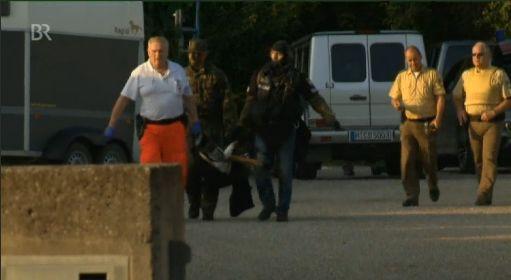 Polizeikräfte tragen den verletzten Hund weg   Foto: Screenshot