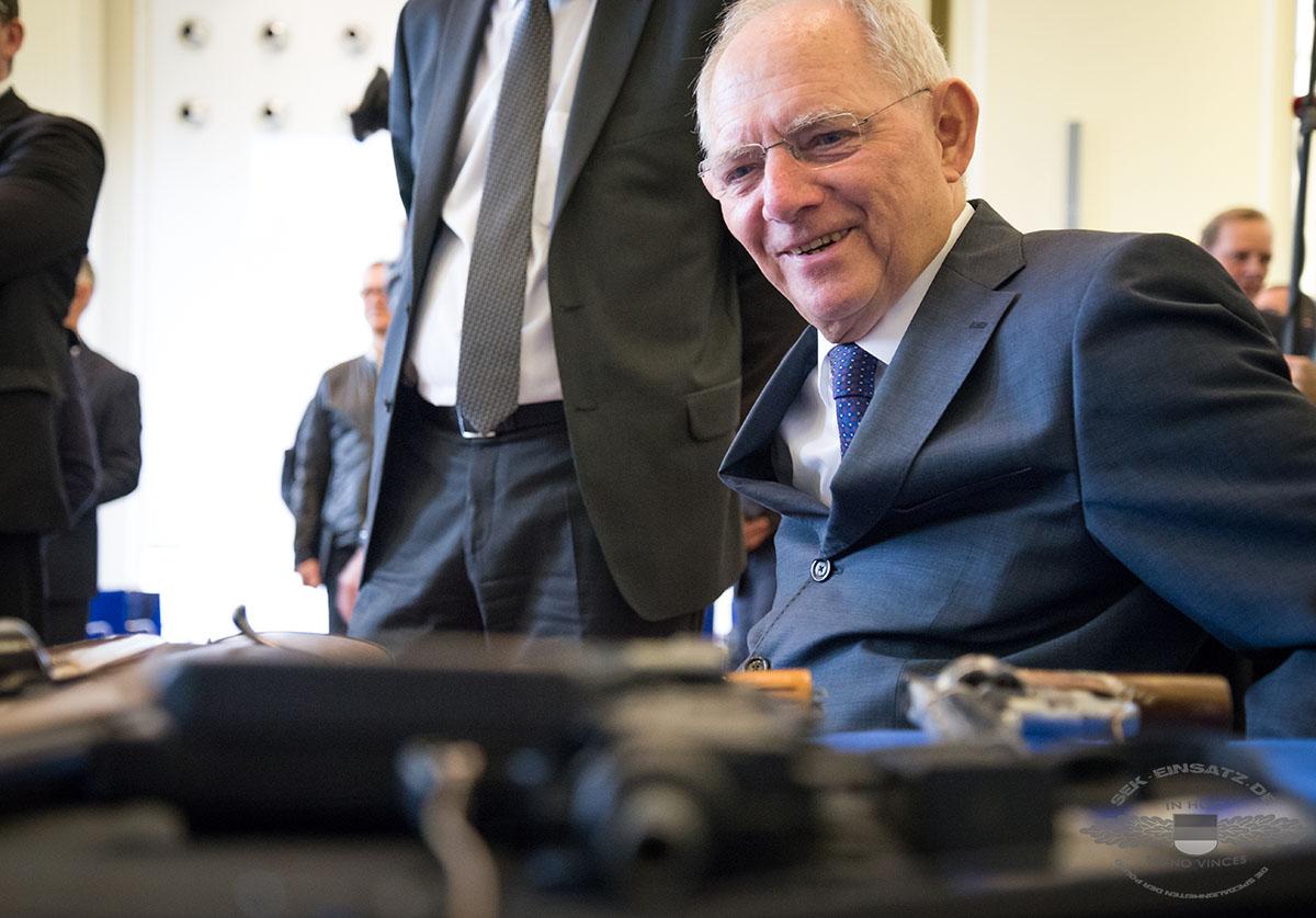 Bundesfinanzminister Wolfgang SchŠuble (CDU) schaut sich am 11.04.2016 in Berlin sichergestellte Schusswaffen auf einem Tisch an. Foto: © Tomas Moll Zuvor stellte der Bundesminister auf einer Pressekonferenz die Bilanz der Deutschen Zollverwaltung fŸr das Jahr 2015 vor.